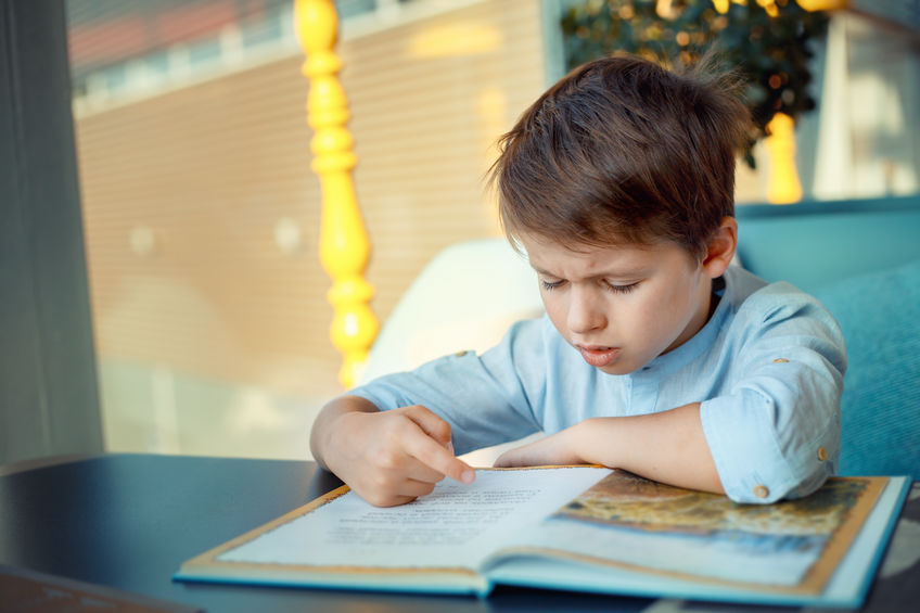 Little boy struggling to reading a book for elementary school