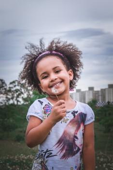 cute happy girl blowing dandelion fluff