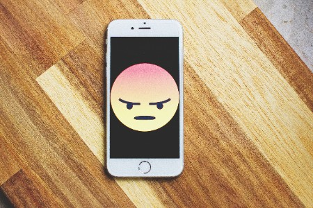 phone on table with angry emoji