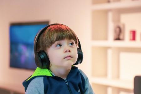 small boy listening to headphones