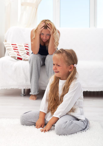 small girl having a tantrum with mother sitting behind her, head in hands