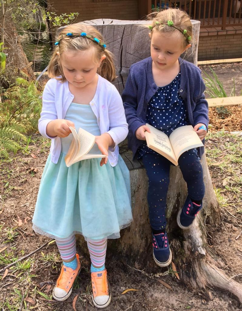 2 girls reading on a log