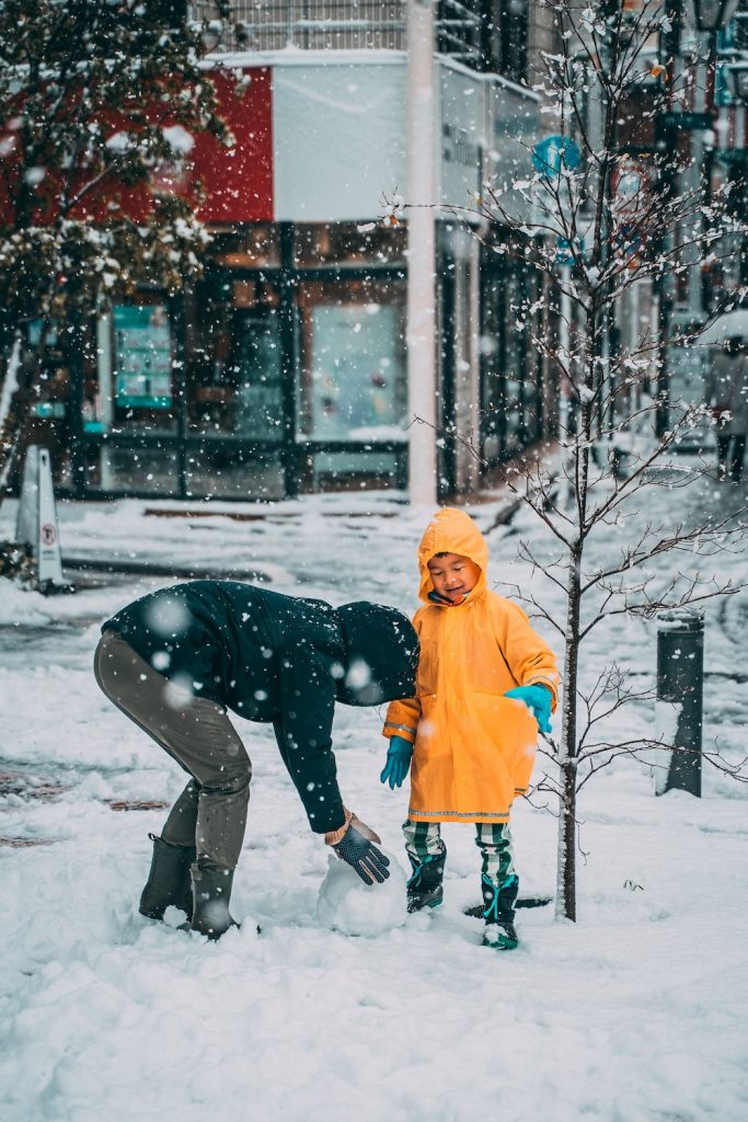 father and child playing in snow