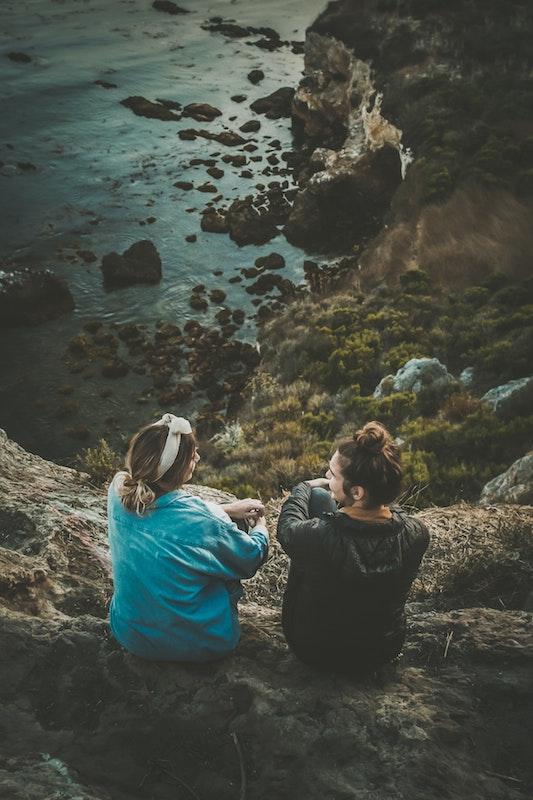 2 women sitting on rocks