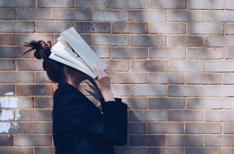 woman with book on face