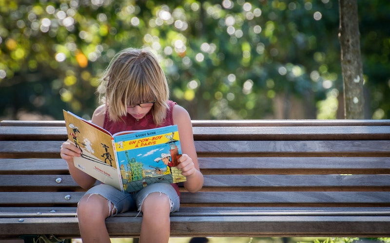 girl in red reading on bench