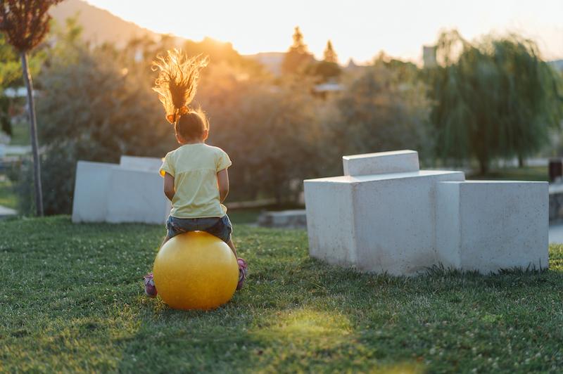 girl bouncing on ball